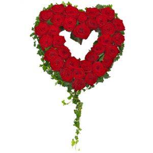 Sorgdekoration med röda rosor och murgröna, format som ett fint hjärta. Murgrönan ramar in det fina rosenhjärtat.