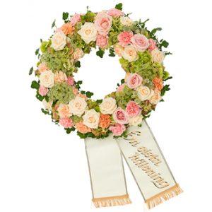 Begravningskrans med pastellfärgade rosor, nejlika, hortensia, slöjsilja och dekorativa gröna blad.