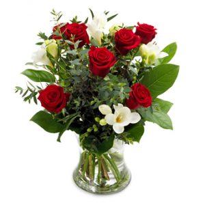 Bukett med röda rosor, vit freesia och grönt.