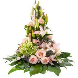 Hög sorgdekoration med pastellfärgade blommor; rosor, liljor, nejlior, prärieklockor och gröna derkoationsblad.