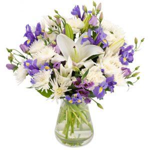 Söt bukett med blandade blommor i vita och ljuslila nyanser.