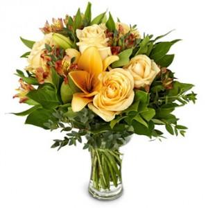 En bukett i milda gula toner, blandade blomsorter.