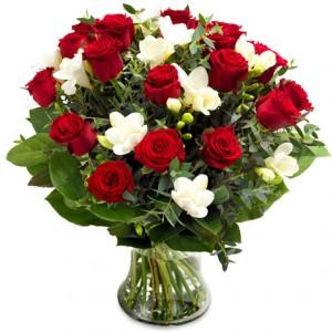 Stor bukett med röda rosor och vita fresior tillsammans med grönt.