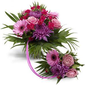"""En familjebukett med en större """"huvudbukett""""+en sammanlänkad mindre barnbukett. Rosor, gerberor och krysantemum i lila och rosa toner. Buketten finns i tre olika storlekar."""