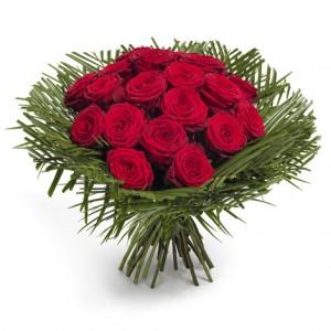 Stor vackert bunden bukett med röda rosor. En manschett av gröna palmblad omger de vackra blommorna.