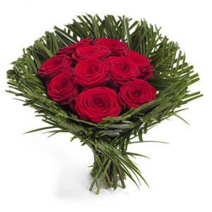 Vackert handbunden bukett med röda rosor och tropiska palmblad knutna som en manschett runt buketten. Finns i tre olika storlekar.
