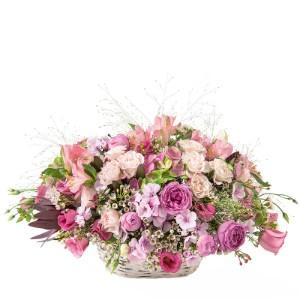 Korg fylld med mängder av blandade blommor i olika rosa nyanser. Blomsterkorgen ingår i Interfloras sortiment av blommor som kan skickas till Monaco.