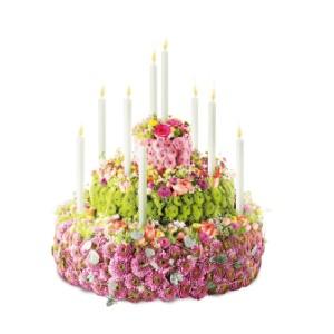 Blomstertårta i tre nivåer, med ljus nedstoppade i tårtan. Ingen ätbar tårta, bara för ögonen:) Skicka den med ett blombud från Interflora. Den ingår i Interfloras Tysklandssortiment.