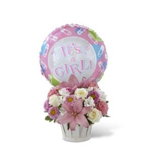 """Arrangemang i en korg med blandade blommor i rosa och vitt + en balong med texten """"It's a girl"""""""