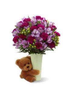 Stor bukett med blandade blommor i vas (vasen ingår). Plus en jättesöt nalle som kramar vasen:) Produkten ingår i Interfloras utlandssortiment för USA.