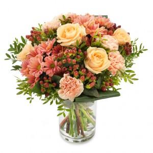 En bukett med blandade blommor i varma toner, aprikos-rosa färger.