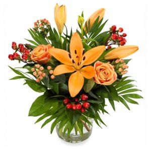 Bukett med blommor i varma toner - orange och rött. På bilden rosor o. liljor i orange tillsammans med röda bär (exempelbild).