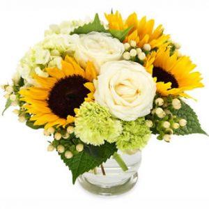 Bukett med solrosor och rosor, gula och vita färgtoner.
