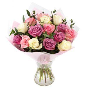 Bukett med rosor i blandade pastellfärger. Buketten är inslagen i papper och cellofan.