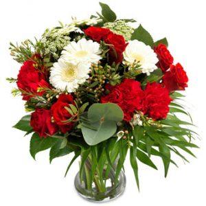Bukett med röda rosor och nejlikor, vit gerbera och småblommigt.
