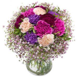Rundbunden bukett med nejlikor i lila och rosa, tillsammans med brudslöja.