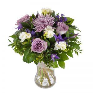 Bukett med blandade blommor i lila och vitt tillsammans med mycket grönt.