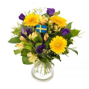 Festlig bukett med blommor i blått och gult. Flaggor i buketten.