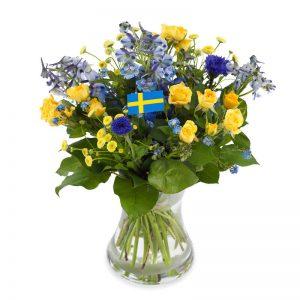 Bukett med blommor i blått och gult. Dekorationsflaggor i buketten.