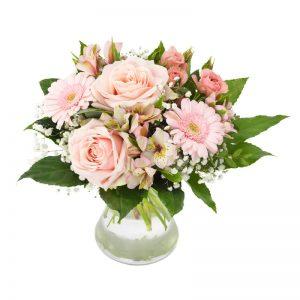 Bukett med rosa rosor och rosa germini tillsammans med småblommigt vitt och gröna blad.