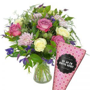 Presentset med blombukett med blandade blommor i ljusa, milda färger +en strut choklad.