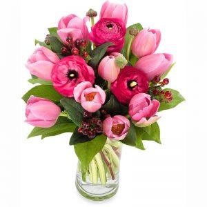 Bukett med tulpaner och ranunkler i rosa nyanser tillsammans med gröna blad. Finns att beställa som blombud hos Euroflorist, en väletablerad blomsterförmedlare på nätet med lång erfarenhet av blomsterförmedling.