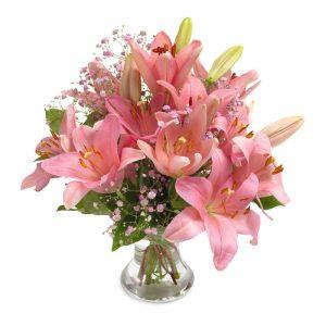 Bukett med rosa liljor, brudslöja och gröna blad.