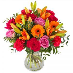 Stor bukett med blandade blommor i rött, rosa och orange tillsammans med gröna blad. Ur Euroflorists sortiment.