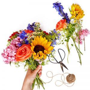 Bukett med blandade blommor i mixade, glada färger. Floristen väljer säsongsblommor - ett alternativ hos Euroflorist.