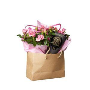 Presentpåse med rosa krukrosor och en chokladstrut. Från Interflora