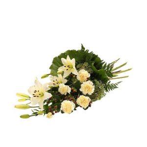 En vacker, vit sorgbukett med nejlikor, lilja, sedum och grönt. Blommorna hittar du bland Interfloras alla vackra begravningsblommor.