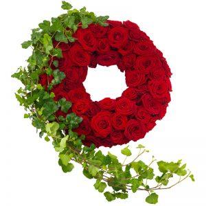 Begravningskrans fylld med röda rosor, ackompanjerade av en fin sträng av murgröna. Kransen finns att beställa hos Euroflorist, en av våra största blomsterförmedlingar på nätet.