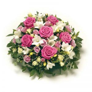 Begravningsdekoration i form av en rund kudde, med blommor i milda färger (rosa, vitt), t ex rosor, fresia och årstidens gröna blad. Skicka dekorationen med bud till aktuell begravning - beställ behändigt direkt i Euroflorists e-butik.