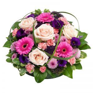 Rund sorgdekoration med blommor i rosa, cerise och lila (rosor, gerbera, prärieklocka och gröna blad). Dekorationen ingår i Euroflorists soritment av begravningsblommor.