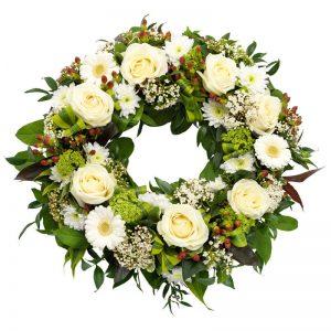 Begravningskrans med blommor i vitt; rosor, gerbera, krysantemum, snöbollsbuske, hypericum. Kransen kan du skicka med ett blomsterbud från Euroflorist - beställ snabbt och enkelt online.