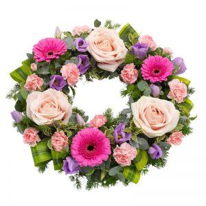Begravningskrans med blommor i rosa, lila och cerise; rosor, germini, prärieklocka, nejlikor tillsammans med säsongsgrönt. Begravningskransen ingår i Euroflorists sortiment av begravningsblommor.