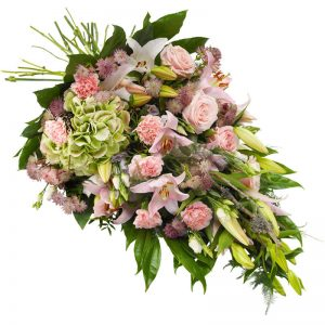 Begravningsbukett med blommor i rosa och cerise; lilja, nejlika, rosor, prärieklocka, astrantia tillsammans med gröna blad. Buketten finns att beställa online hos Euroflorist.