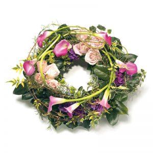 Begravningskrans med blommor i lila och rosa; allor, rosor, hortensia och säsongens grönt. Kransen finns att beställa som blomsterbud hos Euroflorist.
