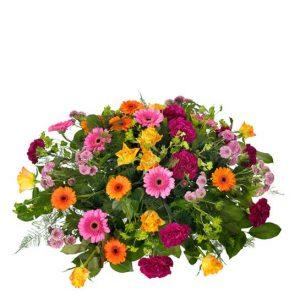Rund, färgglad sorgdekoration med germini, rosor, nejlikor och santini i rosa, cerice, gult och orange tillsammans med gröna blad. Ingår i Interfloras utbud av begravningsblommor.