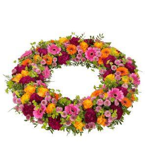 Begravningskrans med blandade blommor i mixade, glada färger; rosor, germini, santini och grönt. Kransen ingår i Interfloras utbud av begravningsblommor.