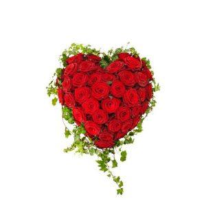 Begravningsdekoration i form av ett hjärta. Härtat är fyllt med röda, vackra rosor och inramas av grön murgröna. Begravningshjärtat finns att beställa hos Interflora.