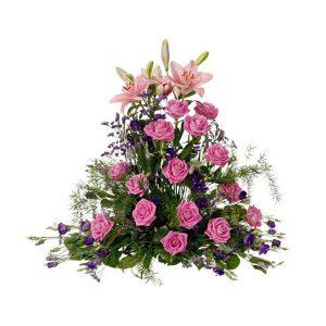En vacker, hög sorgdekoration med liljor, rosor, prärieklockor och limonium i rosa-lila färgtoner tillsammans med grönt. Dekorationen finns att beställa som blombud hos populära Interflora.