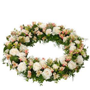 Begravningskrans med nejlikor, rosor och alstromeria i milda färger (ljus cremefärgade och aprikosa färgtoner). Kransen ingår i Interfloras utbud av begravningsblommor.