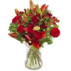 Blombukett med röda liljor, röda rosor, röda bär och gröna blad. Ur Euroflorists sortiment av höstblommor.