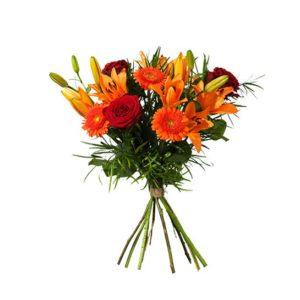 Bukett med blommor i orange och rött; asiatisk lilja, rosor och germini. En höstbukett från Interflora.