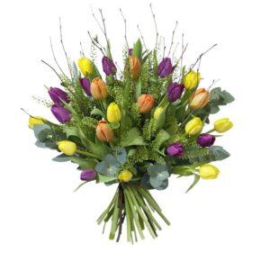 Färgglad påskbukett med tulpaner i blandade färger tillsammans med grönt. Du hittar blommorna i Interfloras e-butik.