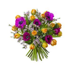 Påskbukett med blommor i orange och lila; tulpaner, anemoner och vaxblomma. Blommorna finns hos Interflora.