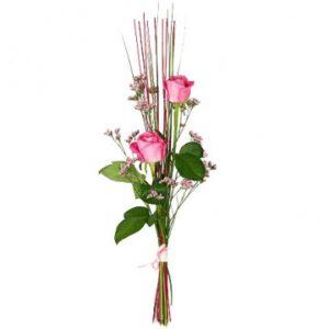 Enkel nivåbukett med två rosa rosor, ljusa snittblommor och dekorationspinnar/strån.