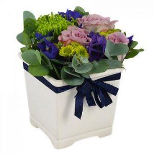 Vit kruka med lågt blomsterarrangemang med blå, lila och cerise blommor. Blått band runt krukan. Ur Florister i Sveriges sortiment.