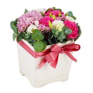 Vit kruka med låg blomsterdekoration med blommor i rosa och vitt. Rosa band runt krukan. Skicka gåvan med ett blomsterbud från Florister i Sverige!